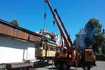 Operace. Těžkotonážní vozy museli jeřábníci nejprve v dokonalé souhře zvednout do vzduchu a umístit na plošiny, odkud už do pavilonu putovaly po kolejích.