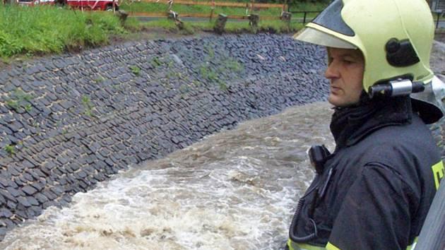 Hasič sleduje rozvodněný potok