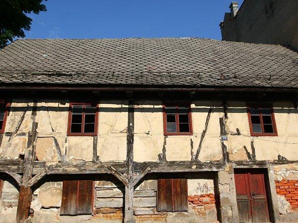 SUNDAT, POPSAT, ZABALIT. Rozebírání podstávkového domu začíná od střechy. Na snímku dělník rozebírá břidlicový štít.
