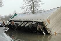 KAMION SE PŘEVRÁTIL. K jedné z březnových nehod došlo u Stvolínek na Českolipsku. Řidič kamionu zde nezvládl mokrý povrch vozovky a převrátil se do zatopeného rigolu u silnice.