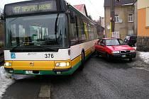 Řidič červeného vozu Škoda Felicie zaparkoval tak, že široký autobus zúženou silnicí neprojede.