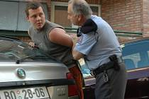 ZATČENÍ. Policista hledá důvody, jak omluvit násilné zadržení jednoho z novinářů, kteří pořizovali fotografie na veřejném místě, což novinářům umožňuje zákon. Na snímku zadržený Emanuel Bořánek.