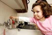 Malá Sára Mádlíková se marně pokouší pustit v kuchyni vodu.