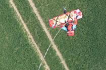 ZÁCHRANÁŘ s pacientem zavěšený na laně pod vrtulníkem.
