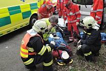 TRAKTOR SKONČIL NA BOKU, TŘI ZRANĚNÍ V NEMOCNICI. Na snímku zraněný řidič v péči záchranářů. Policista ho podrobil dechové zkoušce na alkohol.