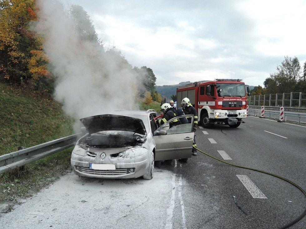 Požár osobního auta na frekventované silnici.