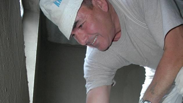 K NASTĚHOVÁNÍ NA PODZIM. Nyní zedníci pracují na interiéru bytů. Na snímku nahazuje omítku František Polič.