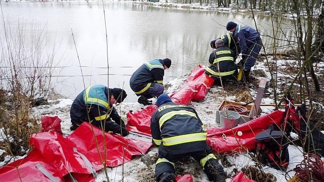 Hasiči likvidují naftu v rybníce.