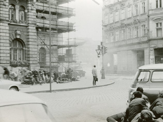 Dobová fotografie zachycuje prchající a ukrývající se lidi na náměstí před libereckou radnicí, jen jeden nemůže jakoby všemu uvěřit.