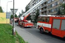 VČASNÝ ZÁSAH ZABRÁNIL ZKÁZE. Profesionální i dobrovolní hasiči zasahovali u požáru v panelovém domě. Protože nebyl majitel bytu, ve kterém hořelo, doma, musel být použit  automobilový žebřík.
