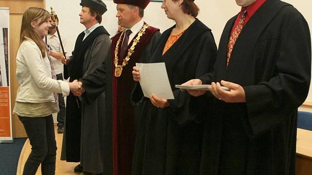 Školáci přebírají diplomy z dětské univerzity.