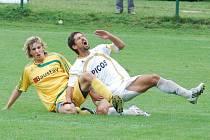 Navzdory tomu, že třetiligový fotbal mnohdy bolí, zůstává kapitán Hlavice Flachbart (v bílém na snímku z utkání v K. Varech) i pro příští sezonu v týmu loňského nováčka.