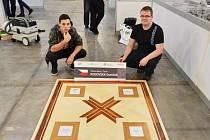 Dominik Koďousek a jeho soutěžní výtvor. Při ME se parkety sestavují do čtverce o straně 1,10 metru. Vpravo mistr výcviku Václav Kulhánek.