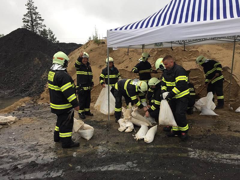 Dobrovolní hasiči už přes hodinu provádějí plnění pytlů pískem. Pytle jsou rozmisťovány do rizikových míst, kde hrozí zatopení.