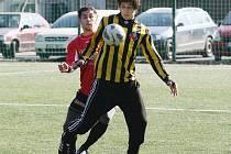 BOŘEK POŽIVIL. Stoper Rapidu v pruhovaném zpracovává míč před nabíhajícím útočníkem Semil.