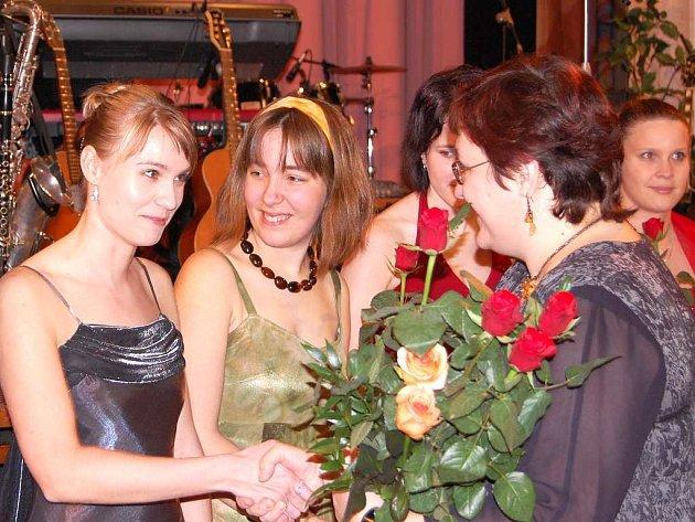 Růže dobrovolnicím předává Drahomíra Blažková, předsedkyně správní rady sdružení Okna. .