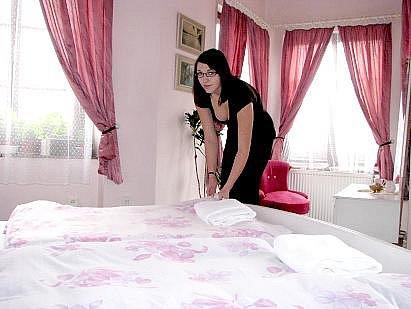 Pokoj pro VIP hosty v jindřichohradeckém hotelu Bílá paní, ze kterého je výhled přímo na zámek, upravuje studentka oboru kuchař číšník Andrea Ťápalová.