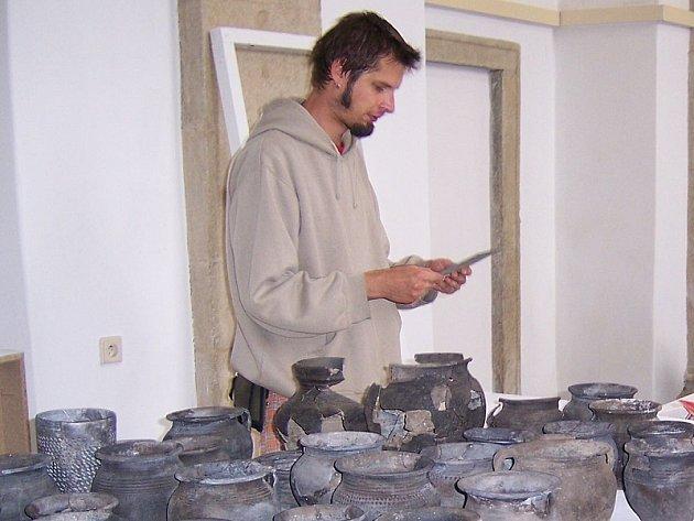 Na padesát hliněných nádob, nalezených loni v archeologické sondě na Masarykově náměstí bude ode dneška až do 21. října k vidění v Muzeu Jindřichohradecka. Na snímku je při instalaci spoluautor výstavy Jakub Valášek.