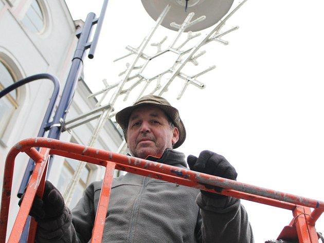VÁNOČNÍ VÝZDOBU instaloval v pátek v Klášterské ulici v Jindřichově Hradci zaměstnanec Služeb města Josef Hůlka.