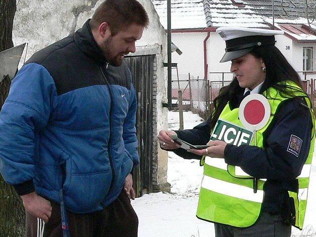 Policejní kontrole v Děbolíně u Jindřichova Hradce neunikl ani řidič Ivan Adam. Podle jeho názoru je policejní dohled důležitý, ale kontroly by měly být hlavně na rizikovějších a nebezpečných místech. Na snímku předkládá doklady policistce Věře Mžikové.