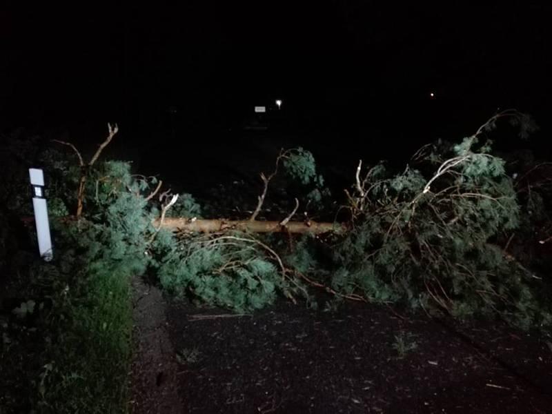 Noční zápolení hatínských hasičů s popadanými stromy na silnici.