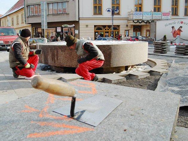 Pohled na rozebranou dlažbu okolo fontány na jindřichohradeckém Masarykově náměstí. Před zimou zde dělníci vyrovnávají povrch.