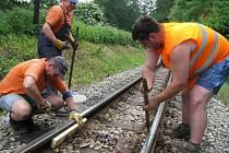 Pracovníci Jindřichohradeckých místních drah dávají odcizené spojky kolejí v zatáčce u zastávky Jindřiš.