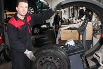 SERVISY mají v těchto dnech pořádně napilno s přezouváním pneumatik. Nejinak tomu bylo včera i v hradecké Autodílně Kreuzer. Na snímku při práci majitel firmy David Kreuzer.