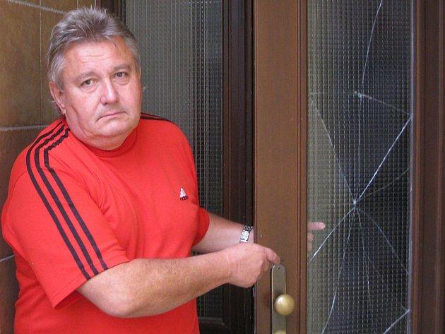 Iniciátor petice Zdeněk Hanzal ukazuje jedny z rozbitých vchodových dveří v panelovém domě na jindřichohradeckém sídlišti Vajgar, které neodolaly řádění vandalů.