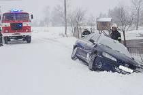 Typická zimní monentka z víkendu. Suchdolští hasiči tahají auto z příkopu.