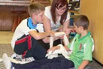 PRVNÍ POMOC.  Jak ošetřit zlomenou ruku si zkoušeli  Robin Kopanič (vlevo) a Miroslav Přibyl z páté třídy. Pomáhala jim  Viola Pšenčíková ze zdravotnické školy.