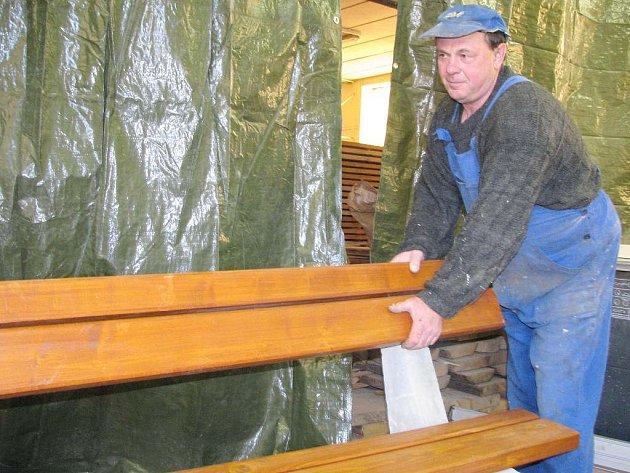 Pracovník jindřichohradeckého Mihosu Jaroslav Vitoň opravuje lavičky a vyměňuje dřevěné části.