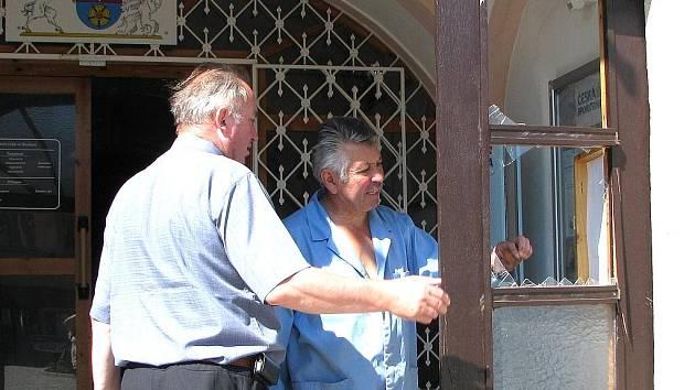 Pohled na vstupní dveře Obecního úřadu ve Studené, kde v úterý v časných ranních hodinách lupiči odcizili bankomat. Starosta obce Josef Rod se sklenářem.