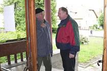 Odborový předák skláren v Chlumu u Třeboně (vlevo) ve dveřích kulturního domu hovoří s poslancem Vítězslavem Jandákem.