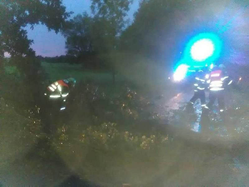 Následky bouřky na jihu Čech v noci z pátku na sobotu budou lidé ještě nějaký čas odstraňovat. Suchdolští hasiči vyprošťují sanitu s pacientem, kterou uvěznily stromy u Mirochova.