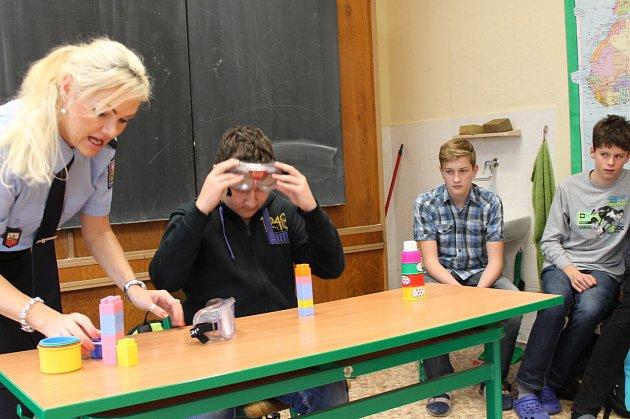 Poskládat kostky s brýlemi, které simulují opilost, není nic jednoduchého. Na snímku s policejní mluvčí Hanou Millerovou si to vyzkoušel žák 8. třídy Ondřej Frid.