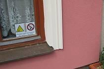Pohled na povinnou nálepku informující o kouření za oknem restaurace U Papoušků v J. Hradci.