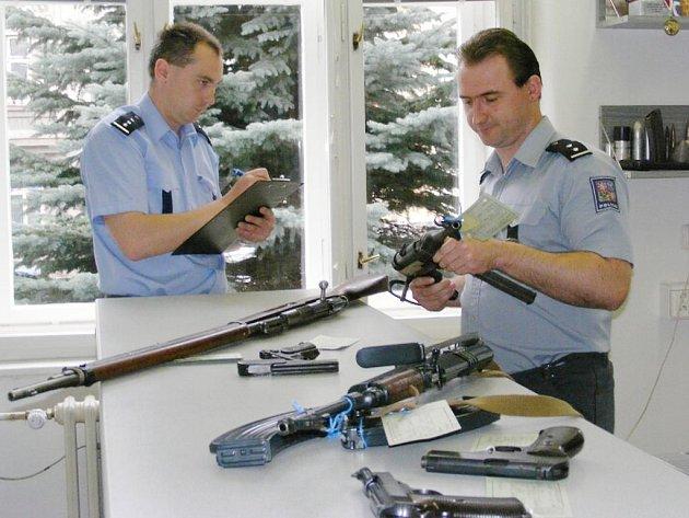 Zbraně, které už na Jindřichohradecku odevzdali lidé policii. Na snímku je ukazují pracovníci oddělení služby pro zbraně a bezpečnostní materiál Jaroslav Sokolík (vpravo) a Josef Tunka.