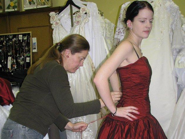 . Majitelka třeboňského svatebního salonu Zdenka Chadtová šaty také šije. Na snímku upravuje večerní toaletu na modelce Veronice.