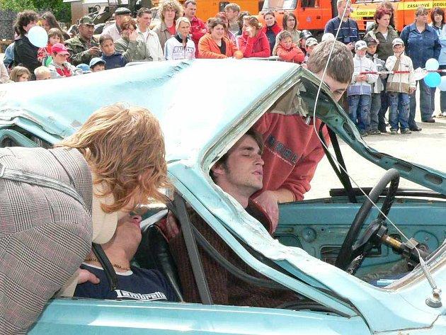 První pomoc zraněným v havarovaném autě.
