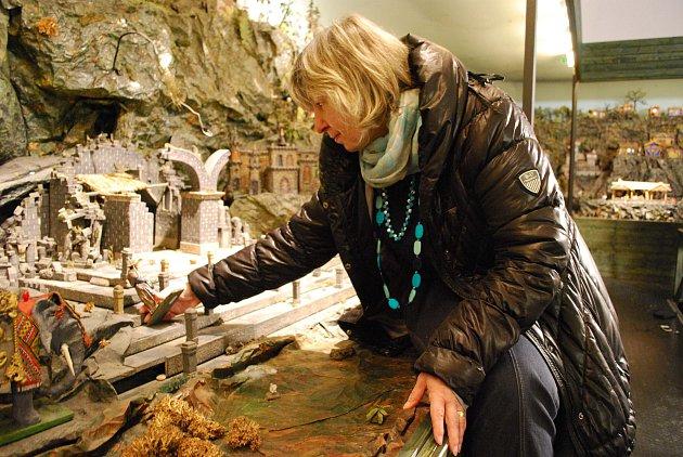 Etnografka Muzea Jindřichohradecká Alexandra Zvonařová u rozebrané ústřední scény betlému a s figurkami.