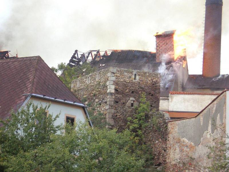 Pohled na plameny šlehající ze střechy pivovaru v Jindřichově Hradci, který 7. září zachvátil požár.
