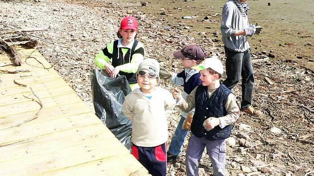 """Nejmenší brigádníci pomáhali vyčistrit dno momentálně vypuštěného rybníky Vajar od větví a """"poklad"""", které do něj naházeli lidé."""