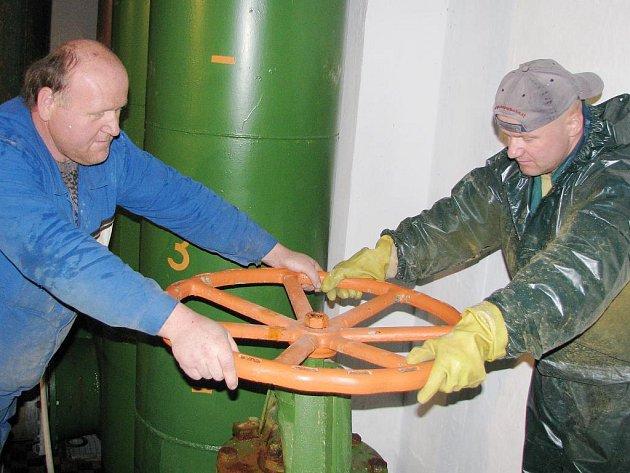 Pracovníci Vodovodů a kanalizací Zdeněk Janda a Petr Pospíšil napouštějí vodu do vyčištěné nádrže.