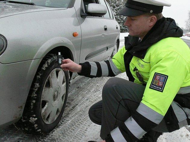 ZIMNÍ PNEUMATIKY a jejich správný vzorek budou celý týden v hledáčku dopravních policistů na Jindřichohradecku. Na snímku ze včerejška kontroluje hloubku vzorku Stanislav Fila.