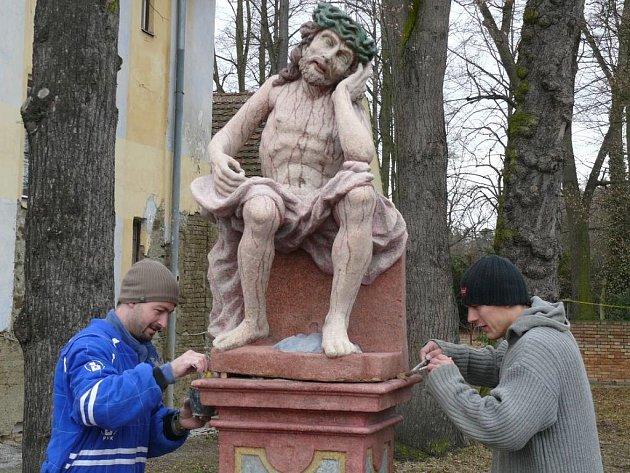 Zrestaurovanou sochu Odpočívajícího Krista osadili restaurátoři Lukáš Hosnedl (v modrém) a Jan Korecký Na Kopečku v Třeboni.