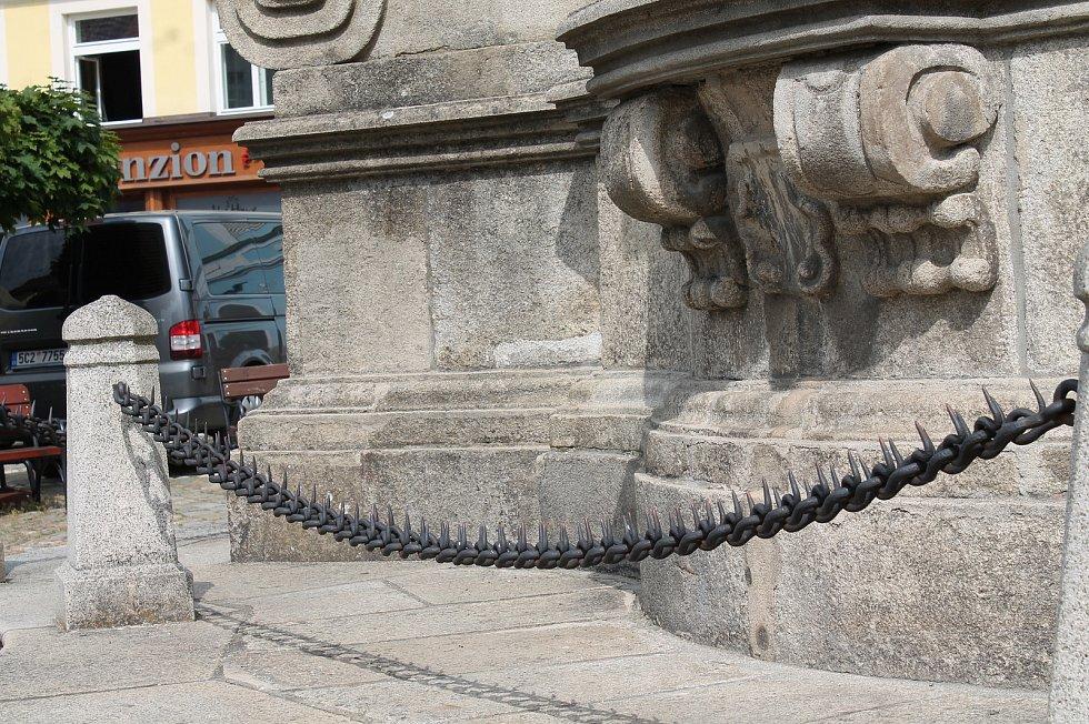 Řetěz s ostrými bodáky ohraničující morový sloup Nejsvětější Trojice.