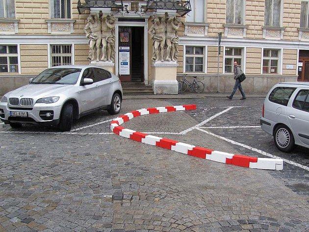 """Pohled na novou úpravu parkovací plochy před budovou  městského úřadu. Parkovací místo vlevo od barevného obrubníku bude ještě """"vymazané""""."""