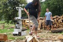 Jednou z mnoha činností v Podcestném mlýně je zpracování dřeva. Výtěžek z něj putuje zpět na podporu komunity. S obrovskými špalky zápasí i Katka.