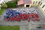 Žáci 1. hradecké základní školy vytvořili k národním kulatinám živou vlajku na dvoře školy.